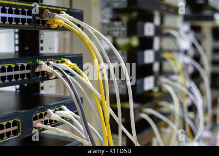 RJ45 cables plugged into switches in rack - Stock Photo
