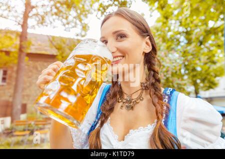 Woman wearing Dirndl drinking beer  - Stock Photo