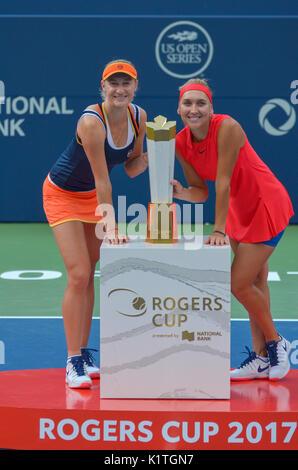 Olympic tennis champions Elena Vesnina and Ekaterina Makarova celebrating their victory with the Maple Leaf trophy. - Stock Photo