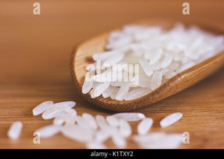 White rice in the wooden spoon. Macro - Stock Photo