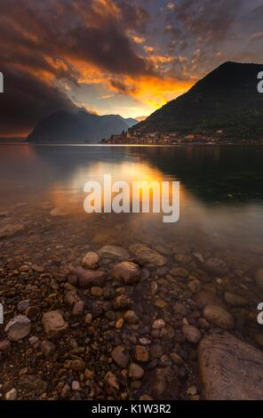 Fiery sunset on the village of Peschiera Maraglio, the tourist capital of Montisola, the island of Lake Iseo in - Stock Photo