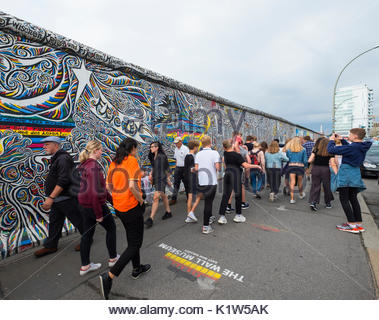 Many tourists walk past mural painted on original section of Berlin Wall at East Side gallery in Berlin, Germany - Stock Photo