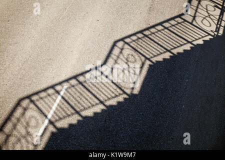 Railing shadow pattern on an empty road asphalt. Simple industrial background