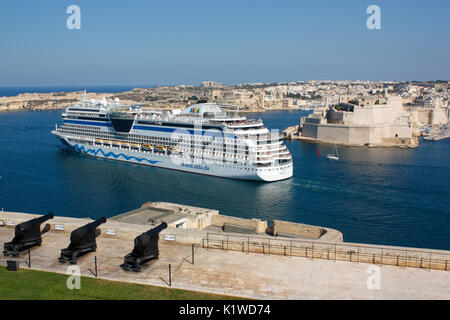 Mediterranean travel and tourism. The cruise ship or liner AIDAstella departing from the Grand Harbour in Malta - Stock Photo