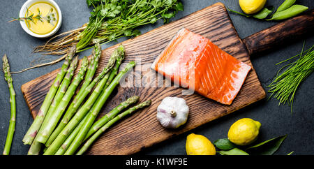 Ingredients for cooking. Raw salmon fillet, asparagus and herbs on wooden board. Food cooking background with copy - Stock Photo