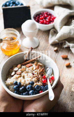 Oatmeal porridge bowl with superfoods in hands. Hands holding bowl of oat porridge with blueberries, almonds, linseed, - Stock Photo