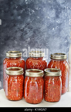 Mason jars canned with homemade salsa sitting on an old white country chair in front of a dark background. Shallow - Stock Photo
