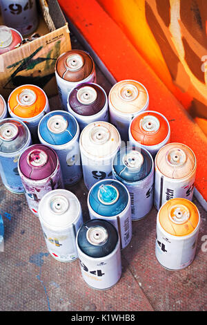 Colourful aerosol spray paint cans by graffiti - Stock Photo