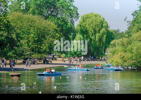 Boating lake London, tourists in pedalos enjoy a summer afternoon on the lake in Regent's Park, London, UK. - Stock Photo