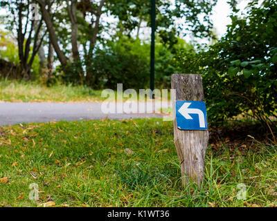 Turn left arrow sign on a stick - Stock Photo