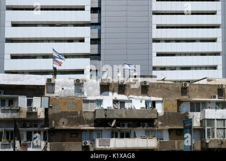 A shabby building stands in stark contrast to modern edifice in downtown Tel Aviv Israel - Stock Photo
