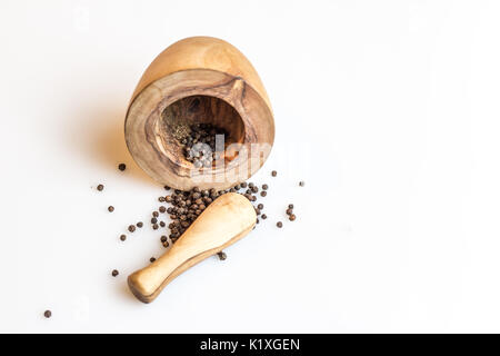 Wood Pestle and Mortar and spilled peppercorns - Stock Photo