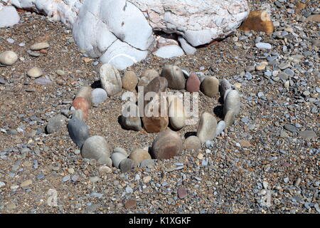 A small arrangement of rounded beach pebbles set out to look like a miniature 'stonehenge' on the beach. - Stock Photo