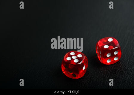 Two red casino poker dice counting seven on a bleack leather background with copy spce for your text - Stock Photo