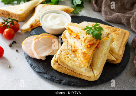 Pressed and toasted double sandwich with chicken, Korean carrots, cheese and tomatoes on a gray stone or slate. - Stock Photo