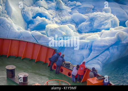 Franz-Joseph Land - 10 July 2016: Tourist cruise in high Arctic. Ship sails close to small iceberg. But we should - Stock Photo