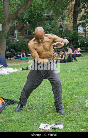 A fit shirtless 67 year old man practices kung fu moves outdoors in Washington Square Park in Greenwich Village, - Stock Photo