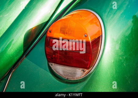 Closeup view of a rear light of an old vintage or retro car. Contrast of orange, red, white and green colors. Sunlit - Stock Photo