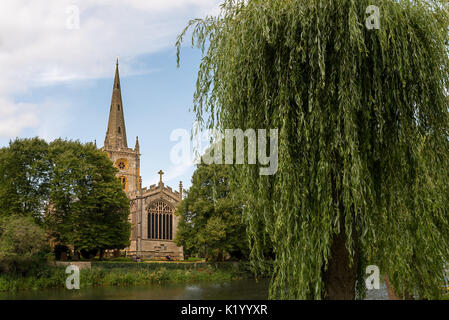 The Holy Trinity Church in Stratford upon Avon as viewed from across the river avon with a small willow tree. - Stock Photo