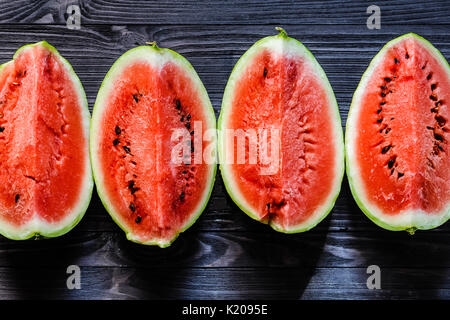 Background of fresh ripe watermelon slices on black wooden table. Top view. - Stock Photo