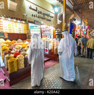 Two Arabs in white robes, Thawb, Spices on an Arab Market, Dubai Spice Souk, Old Market, Old Dubai, Dubai, United - Stock Photo
