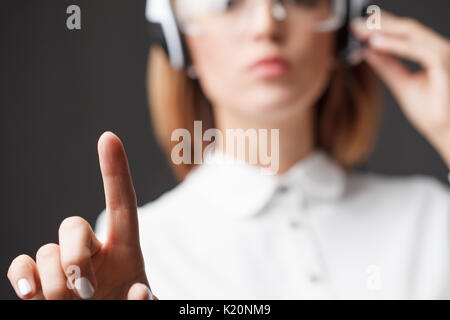 Young businesswoman pressing high tech type of modern buttons. - Stock Photo