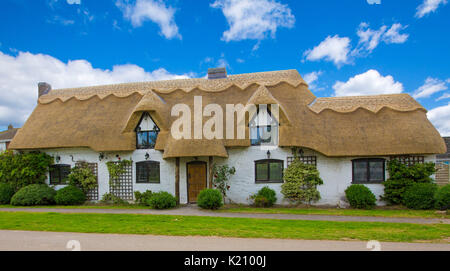 Panoramic view of picturesque thatched cottage with white-washed walls under blue sky at Sutterton, England - Stock Photo