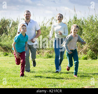 Joyful young parents  with two kids playfully running on the green lawn - Stock Photo