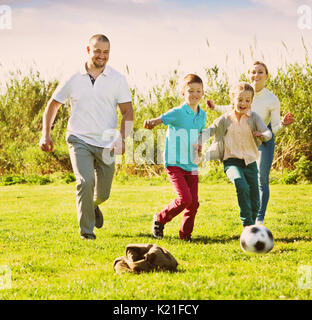 Happy  mother and father with two cheerful kids playfully running after ball outdoors - Stock Photo