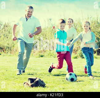 Happy  mother and father with two kids playfully running after ball outdoors - Stock Photo