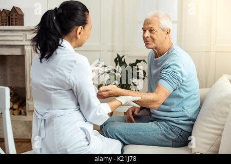 Pleasant nice nurse holding her patients hand - Stock Photo