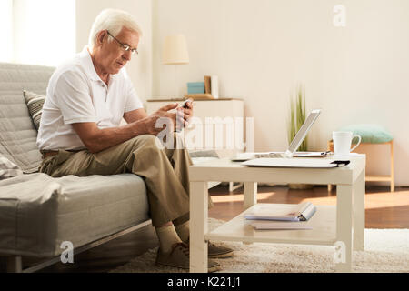 Senior Man Using Smartphone at Home - Stock Photo
