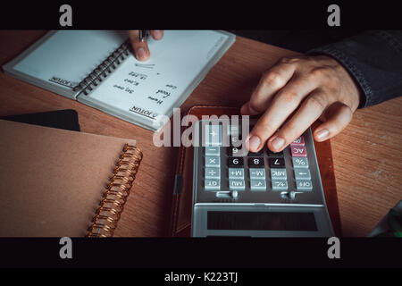 Close up hand Asian man calculate finances and accounting for monthly expenses and charges or cost on notebook with - Stock Photo