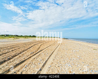 On an empty beach at Caister-on-Sea in Norfolk, England, a group of deep tyre tracks lead off in to the distance. - Stock Photo