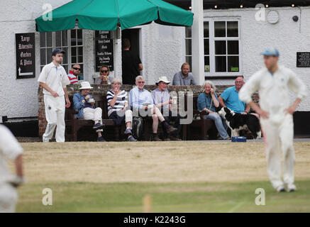 Spectators sat outside the Barley Mow pub watching a village cricket match between Tilford and Grayswood being played - Stock Photo