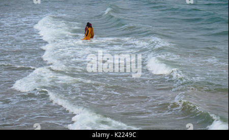 BOURNEMOUTH, UK - AUGUST 22, 2017: Three Asian Woman swim in the sea at Bournmouth - Stock Photo