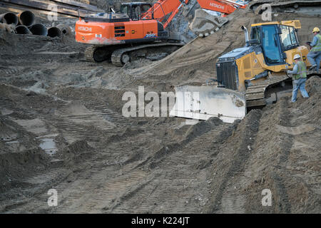 Earth moving machines on site digging a hole in the ground for a building. - Stock Photo