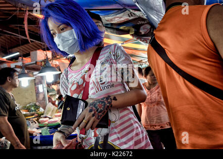 Woman blue hair and tattoos. Fashion Conscious Asian youth. Thailand Southeast Asia. Extreme colored hair - Stock Photo