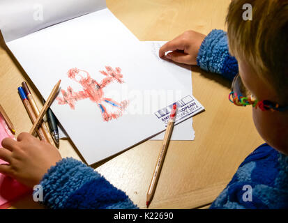 Young boy with glasses at desk admiring his picture of spiderman drawn with coloured pencils on conference scrap - Stock Photo
