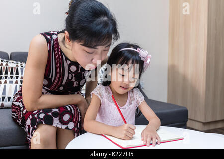 Asian Chinese mother teaching daughter doing homework at home - Stock Photo