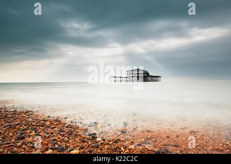 Abandoned (after fire) West pier in Brighton in gloomy day, United Kingdom - Stock Photo