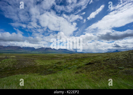 Iceland - Fantastic open range with snow covered mountains behind green flat landscape and blue sky - Stock Photo