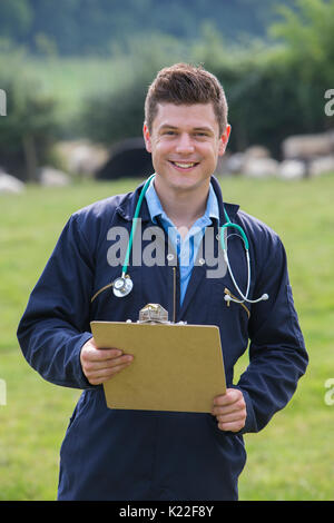 Portrait Of Vet In Field With Sheep In Background - Stock Photo