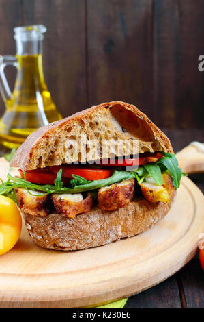 Big sandwich with pieces of meat, arugula, tomato, cereal ciabatta on a cutting board on a dark wooden background. - Stock Photo