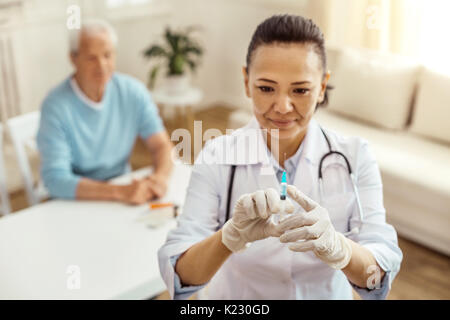 Cheerful positive nurse testing the syringe - Stock Photo