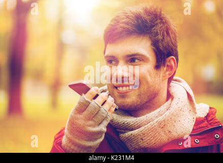 man recording voice on smartphone at autumn park - Stock Photo
