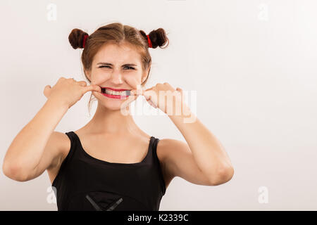 fun beautiful woman grimacing shows her teeth on white background with copy space - Stock Photo