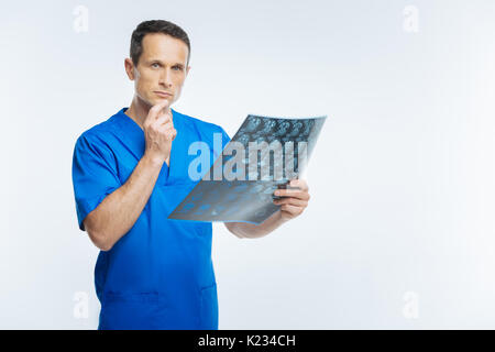 Pensive doctor with x ray scan image looking into camera - Stock Photo