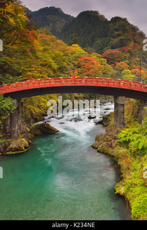 The Shinkyo Sacred Bridge (神橋) in Nikko, Japan over the Daiya River surrounded by bright autumn colors. - Stock Photo
