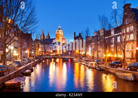 A canal in the red light district in Amsterdam, The Netherlands with the St. Nicholas church at the end. Photographed - Stock Photo